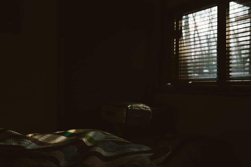 Sunlight filtering through shades in a bedroom.