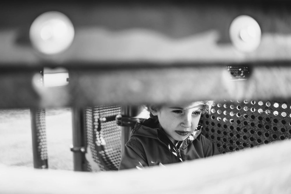 A little girl peeks out from under a play structure.