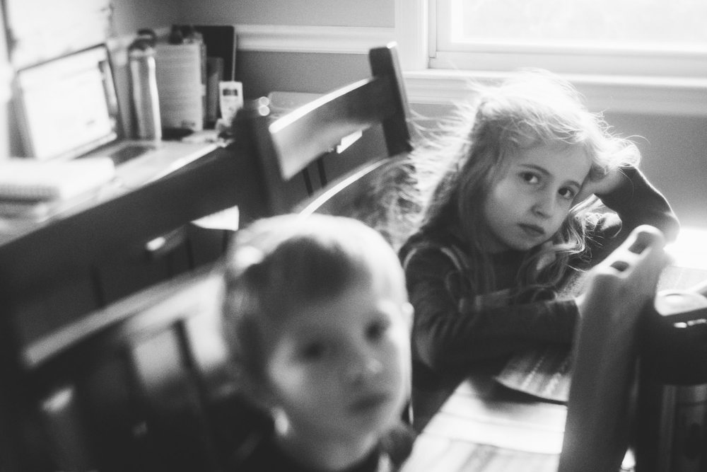 Children play with their tablets at the kitchen table.