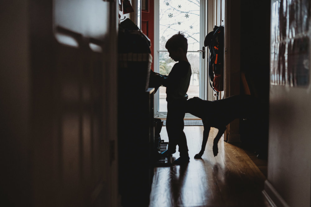 A boy stands in a hallway with his dog.