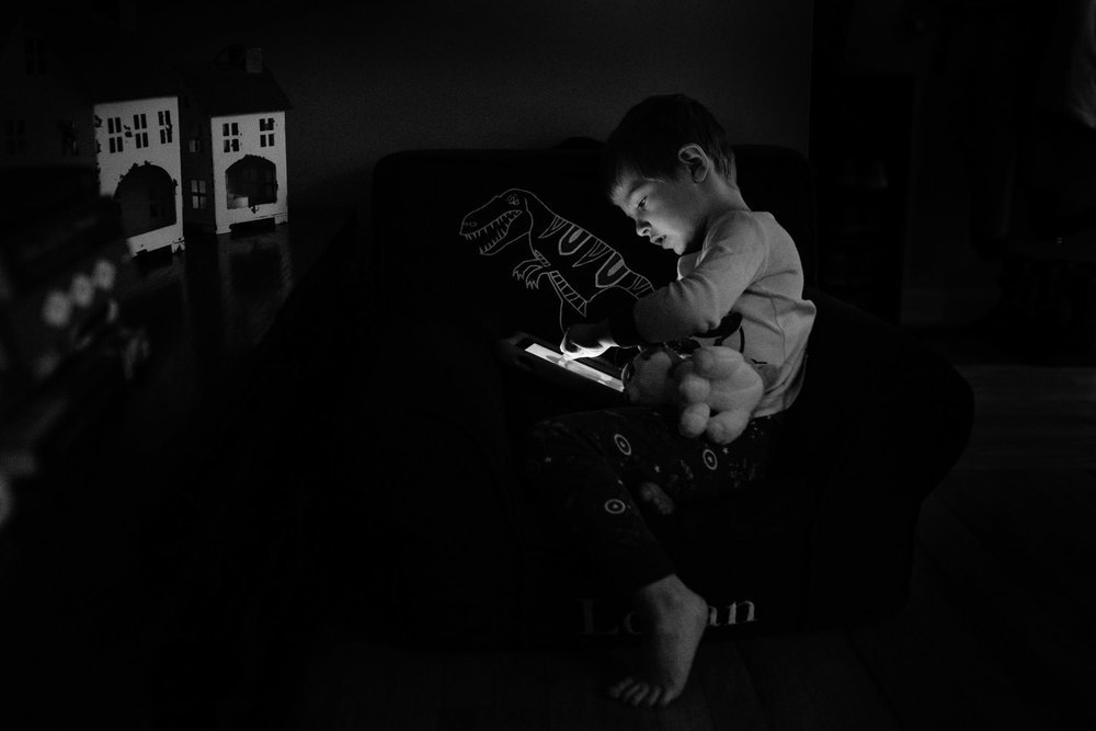 A little boy plays with a tablet.