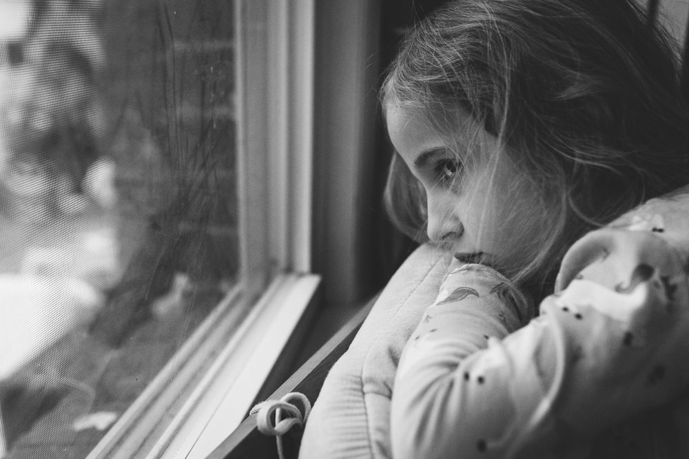 A little girl looks sadly out a window.