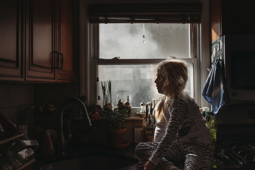 A little girl sits on a kitchen counter.