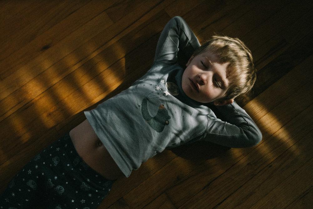 A little boy lies in slivers of sunlight.