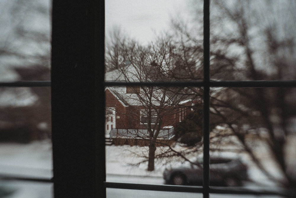 Looking at the snowy neighborhood through a window.