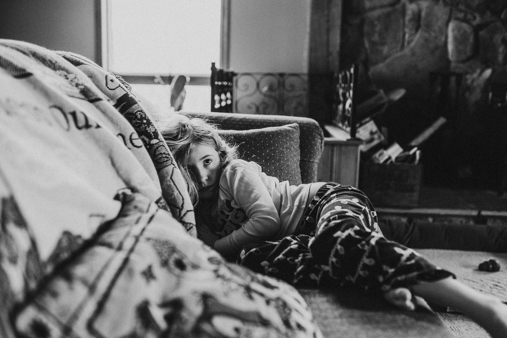 A little girl watches tv on the couch.