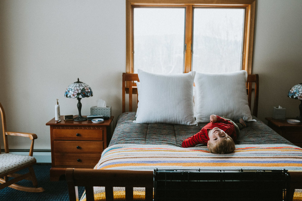 A little boy plays on a big bed.