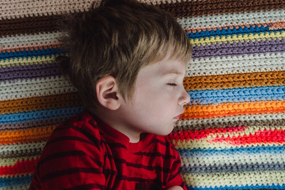 A little boy lies on a striped blanket.