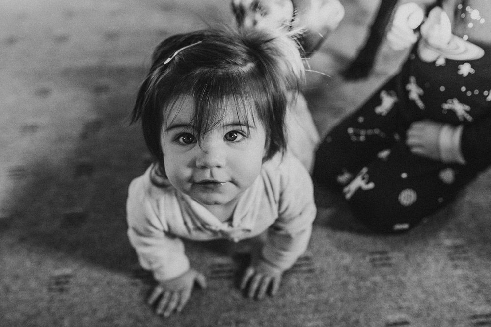 A baby girl looks up at the camera.