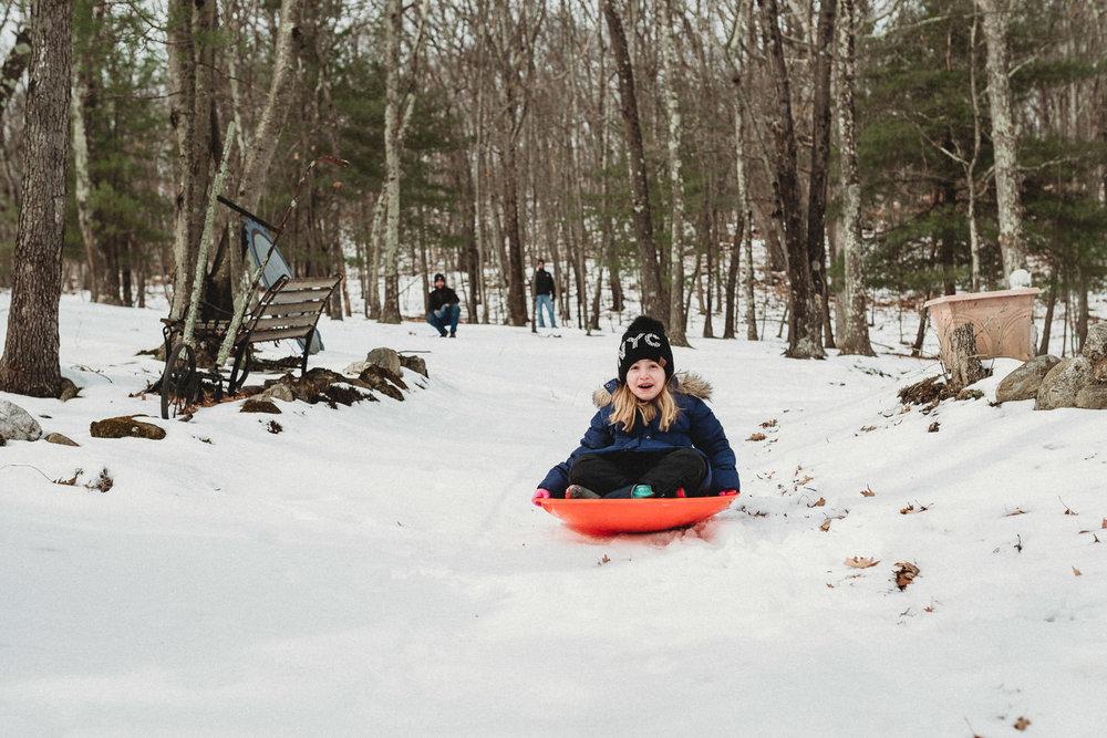 A little girl sleds down a hill.