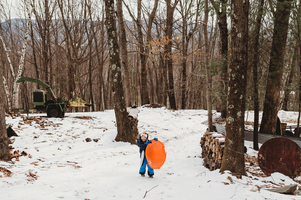 A little boy picks up his sled.