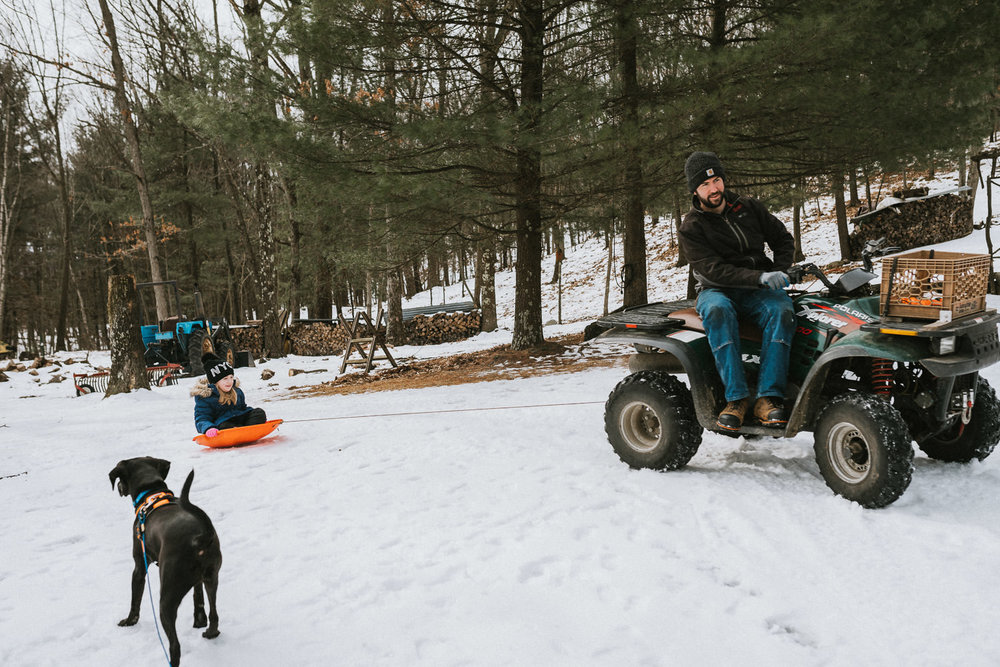 A little girl is pulled on a sled by a four-wheeler.