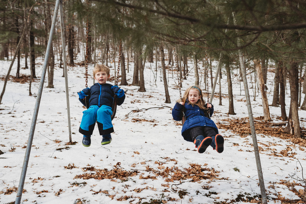 Two children swing on a swingset in the snow.