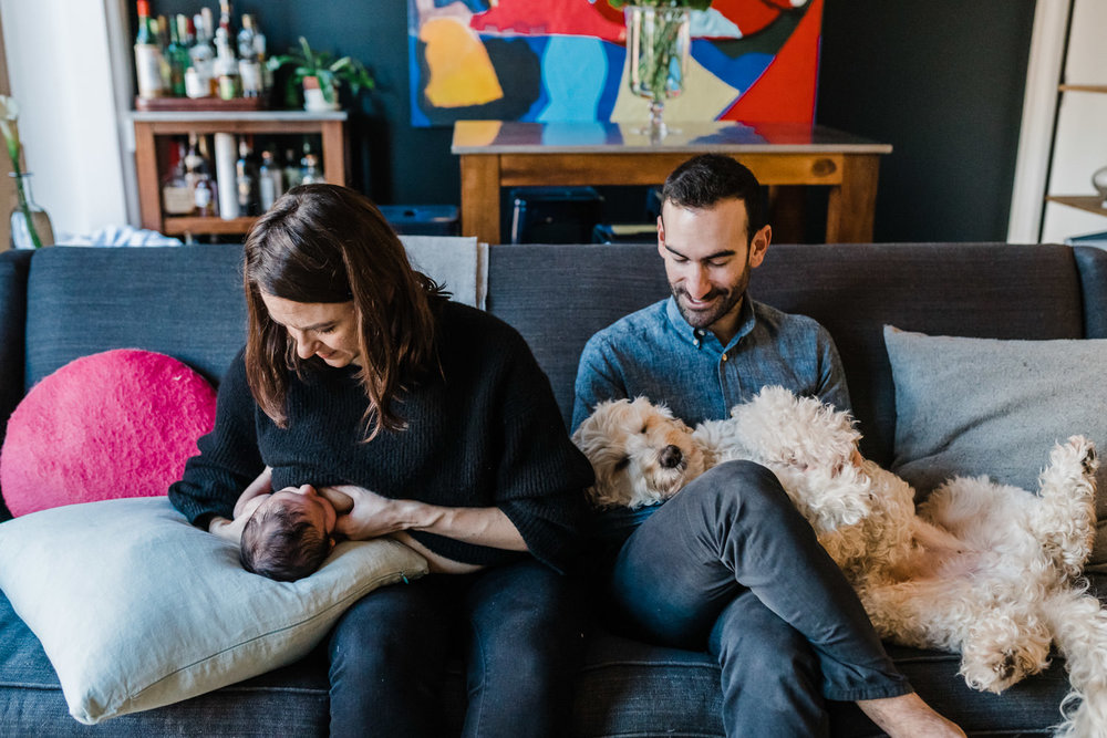A mother nurses her son on the couch next to her husband.