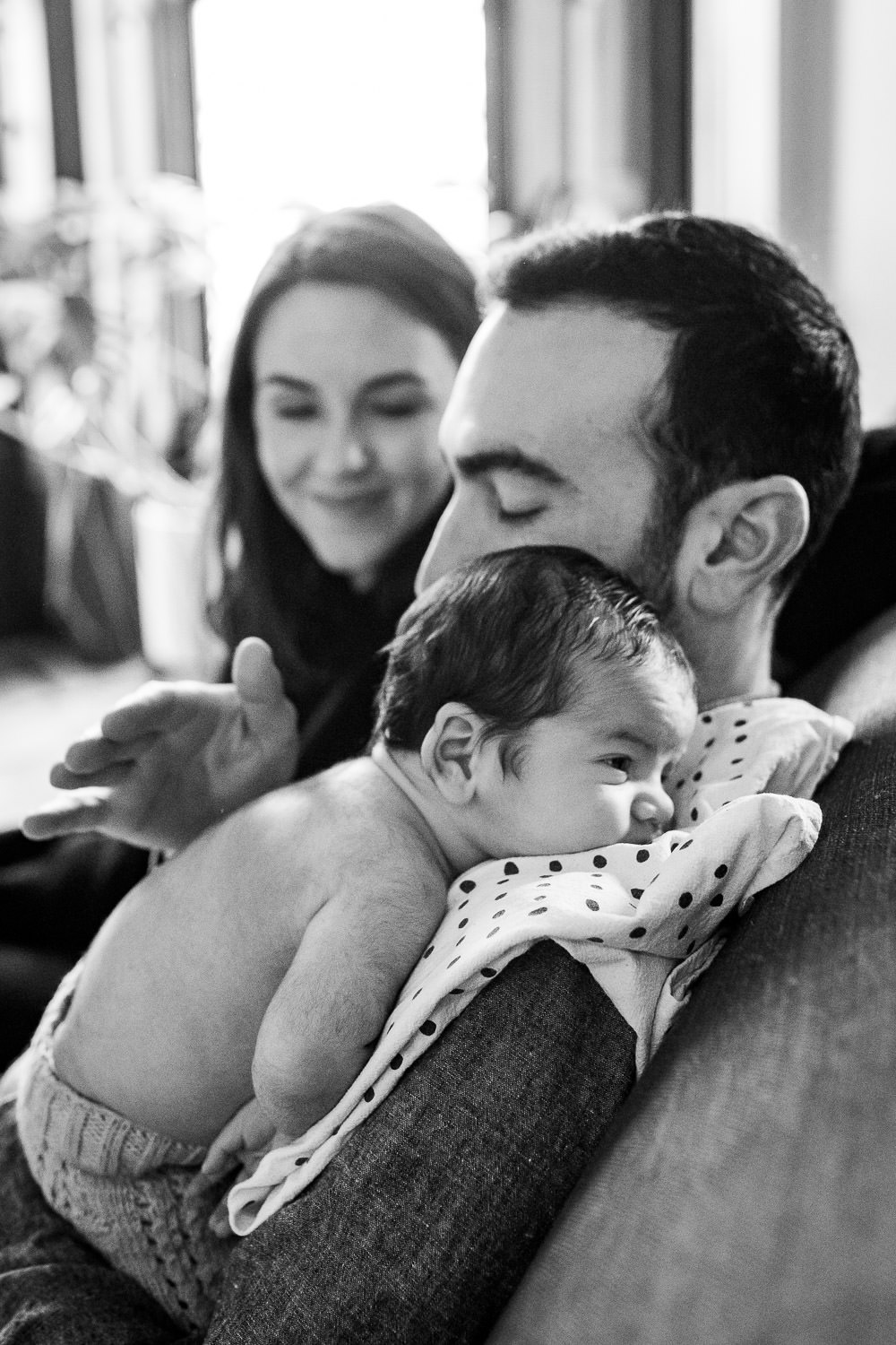 A baby rests on his father's shoulder.