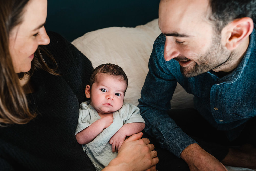 Two parents smile down at their baby boy.