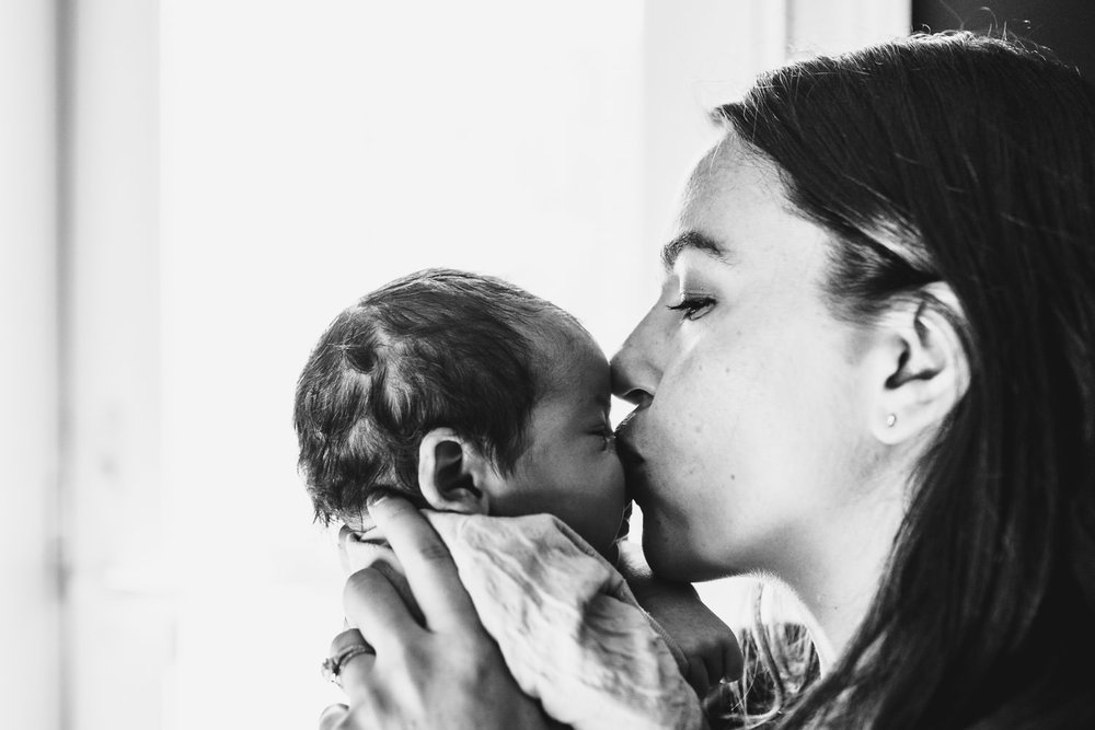 A mother kisses her baby son.