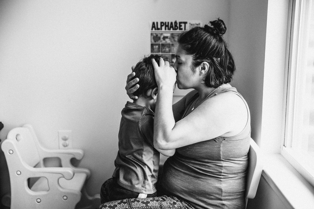 A mother comforts her toddler son.