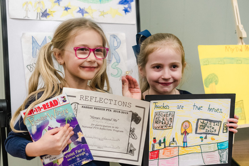 Two little girls hold up their art awards.