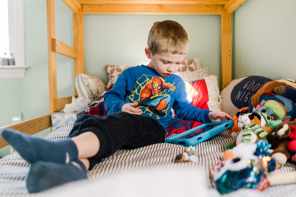 A little boy watches his tablet in bed.