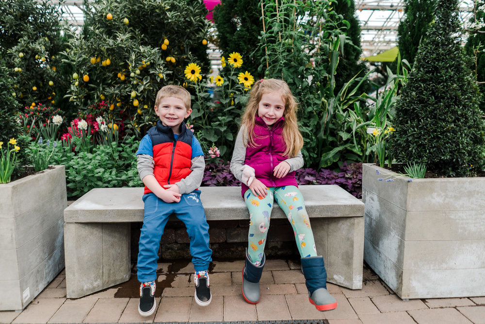 Two children smile from a bench at the Hicks' Flower Show.