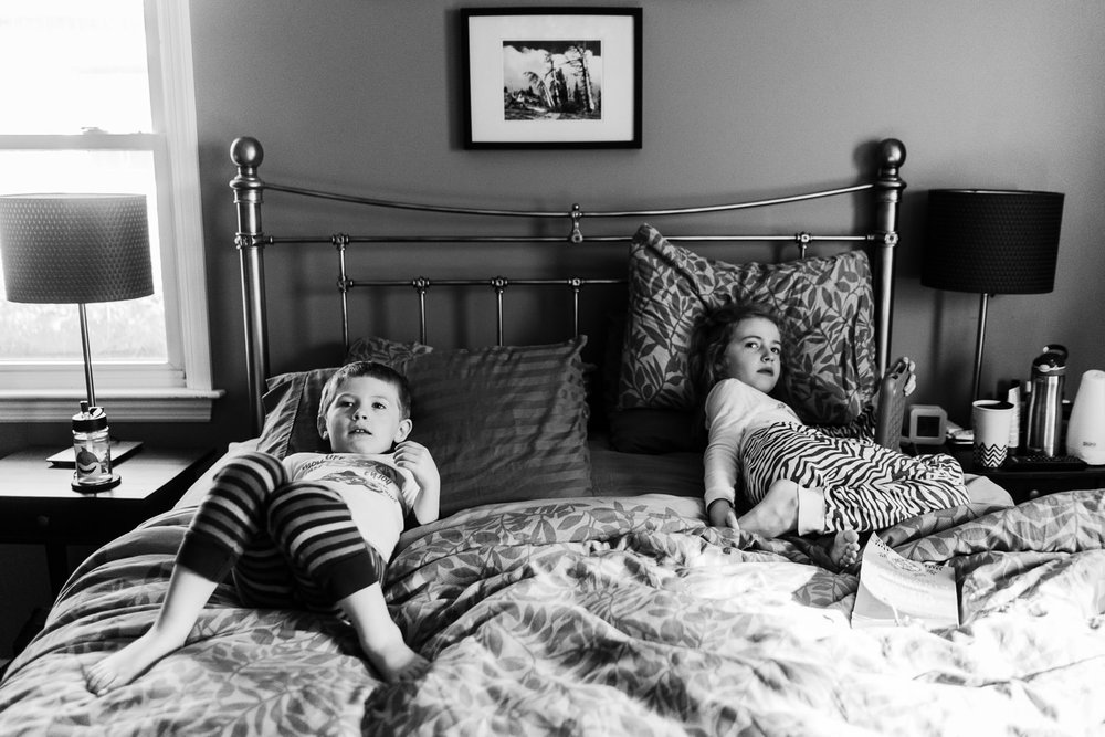 Two kids lie in their parents' bed.