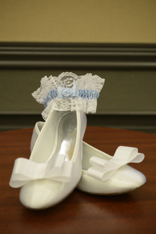 Blue garter around sweet white ballet wedding flats