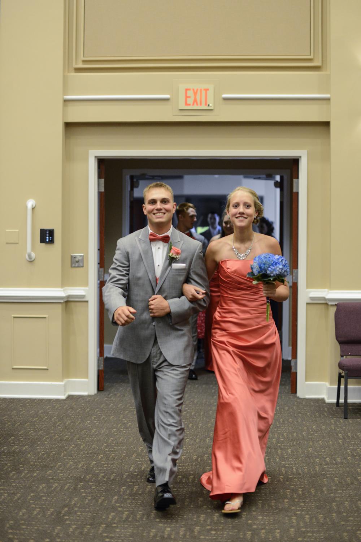 Bridesmaid and groomsman walking into wedding reception