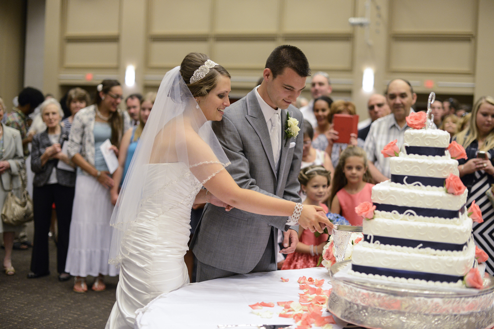 Bride and groom cut coral pink and navy wedding cake at reception