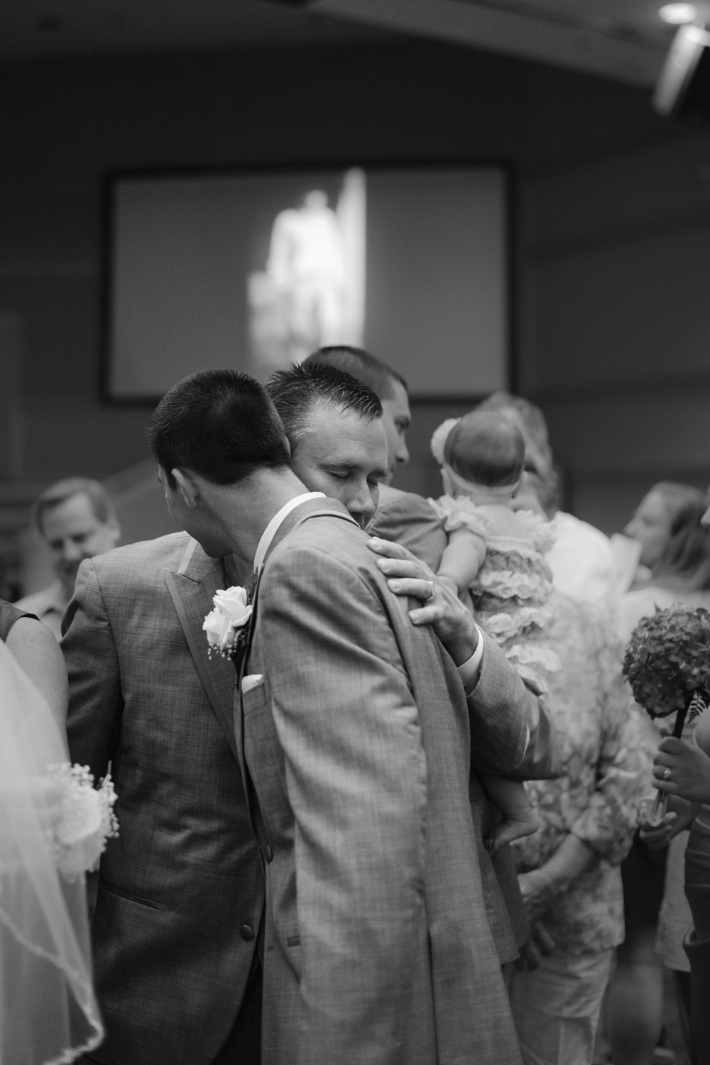 Groom and his father embrace at the wedding reception, black and white