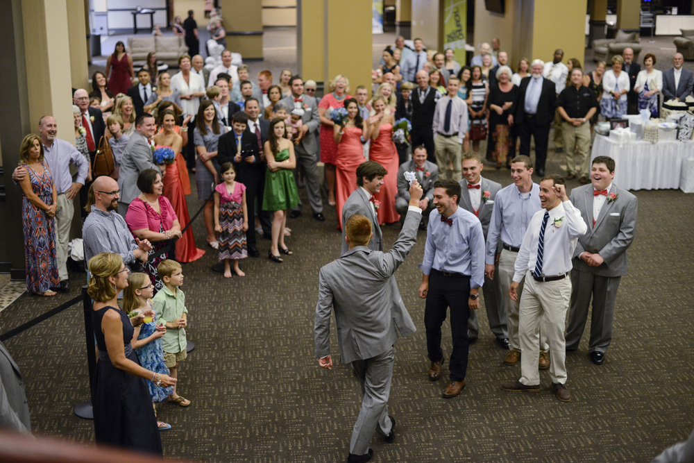 Groomsman catches garter at wedding reception