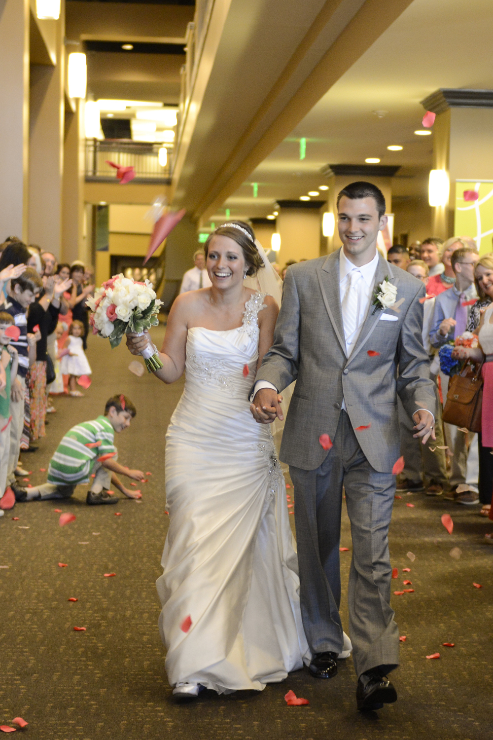 Bride and groom exit in coral pink flower petals
