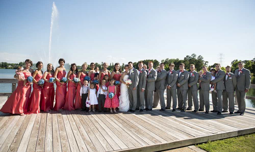Huge bridal party in gray suits and coral pink bowties and dresses by the water in Suffolk, Virginia