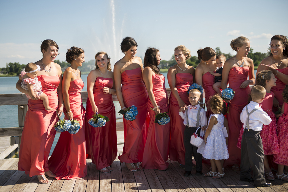 Bridesmaids on a dock in coral pink dresses
