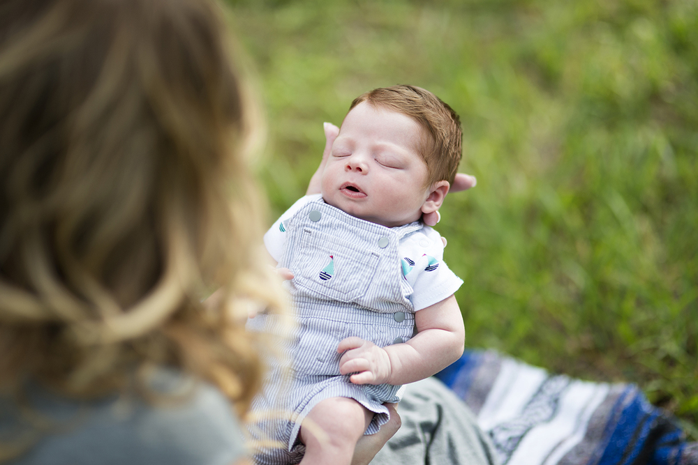 Intimate redhead newborn shot during  family portraits on a picnic blanket in a park
