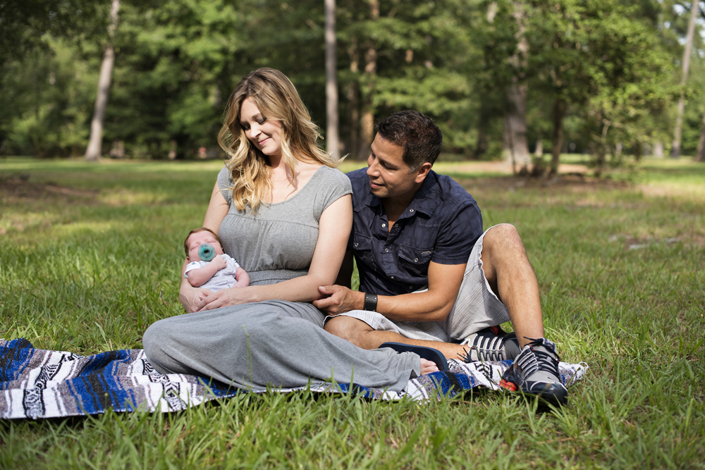 Mother and father with redheaded newborn during  family portraits on a picnic blanket in a park
