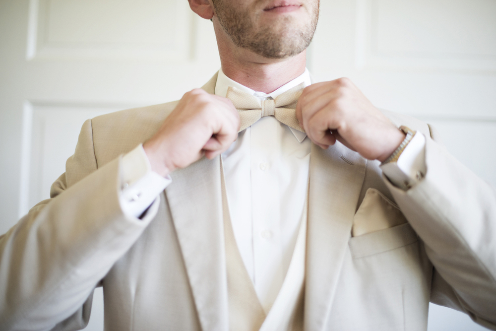Groomsman adjusts his cream white tie  | Portsmouth Woman's Club in Virginia