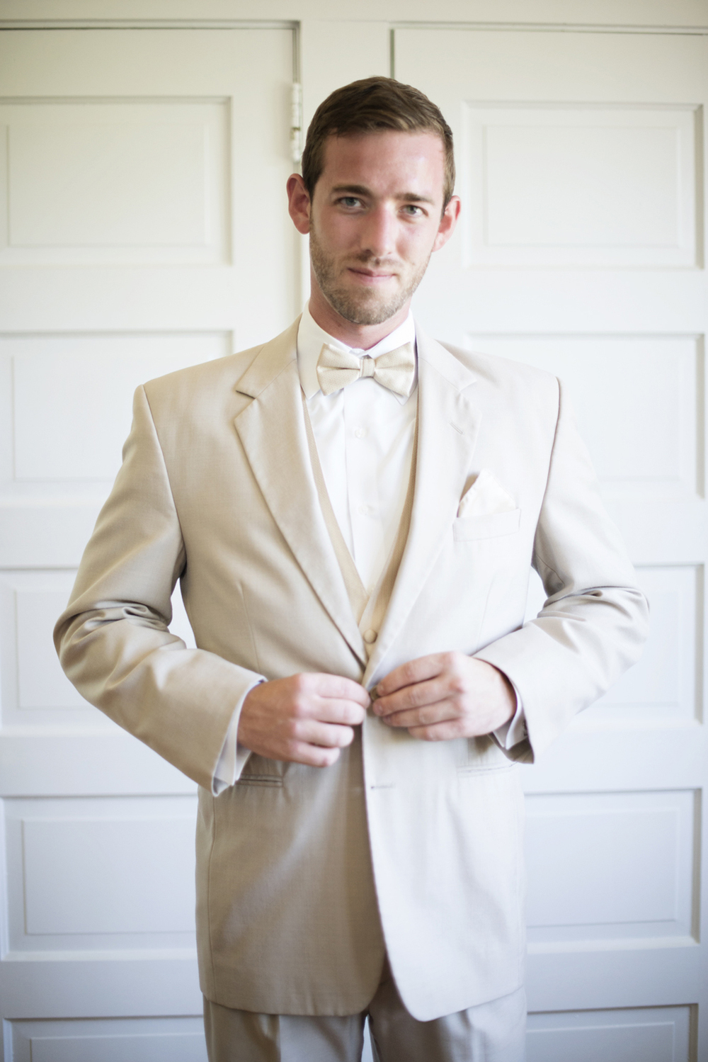 Groomsman buttons his cream white jacket  | Portsmouth Woman's Club in Virginia