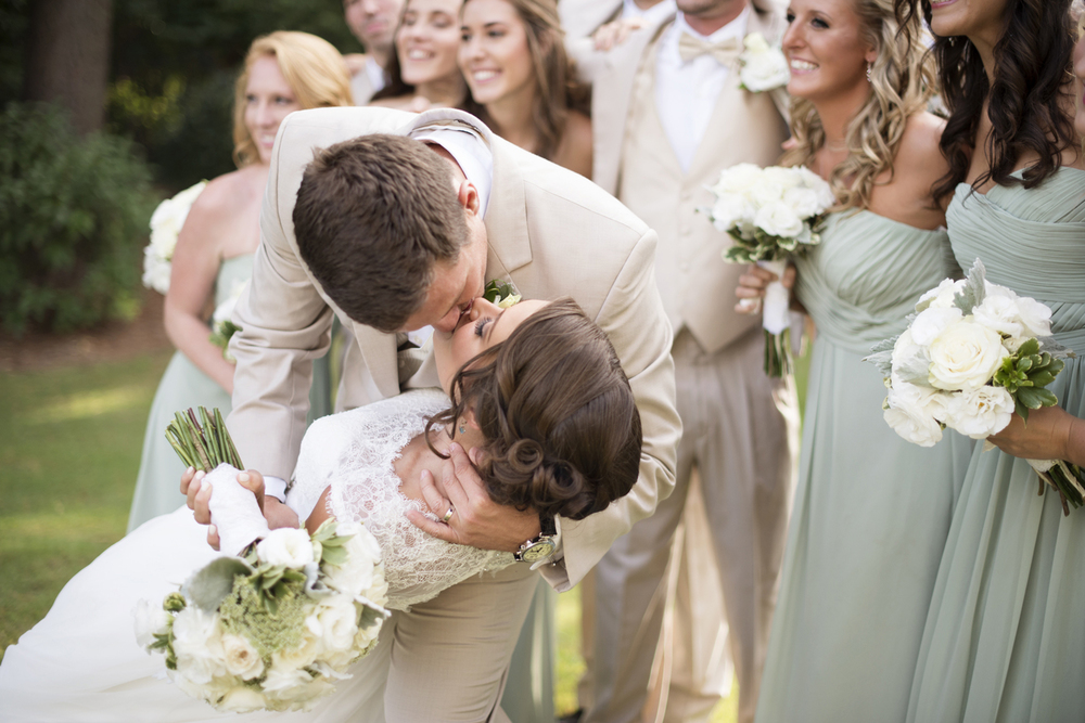 Groom dips his bride for a kiss on their July wedding  | Portsmouth Woman's Club in Virginia