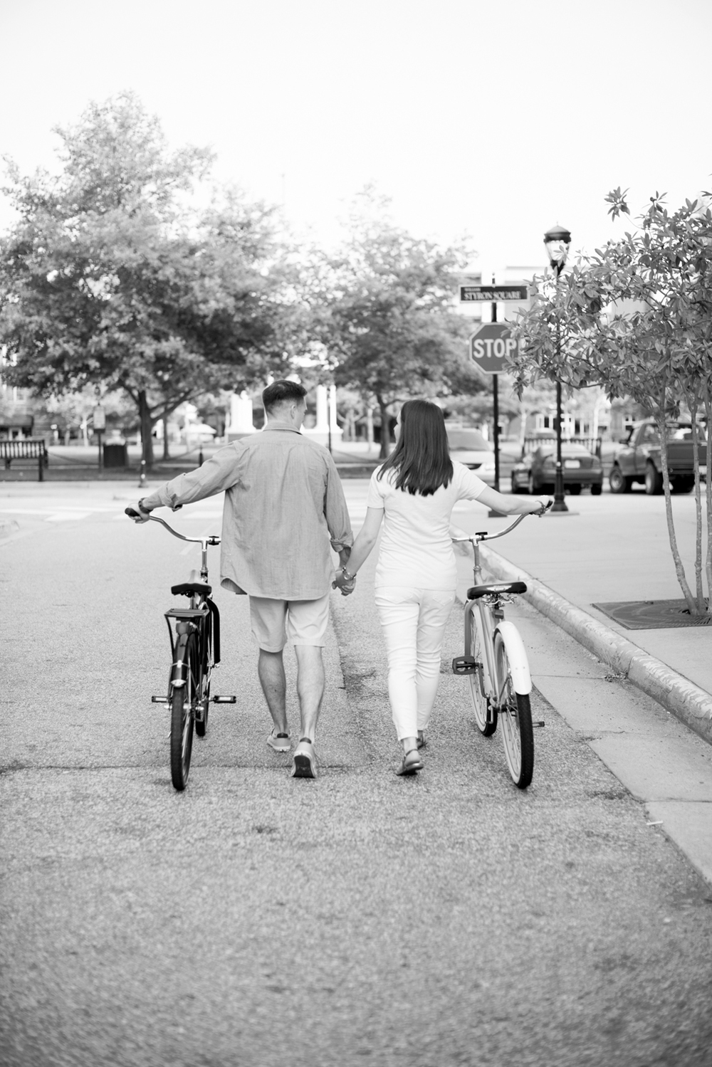 Couple walks with their bikes down a city street in Port Warwick, Newport News, Virginia