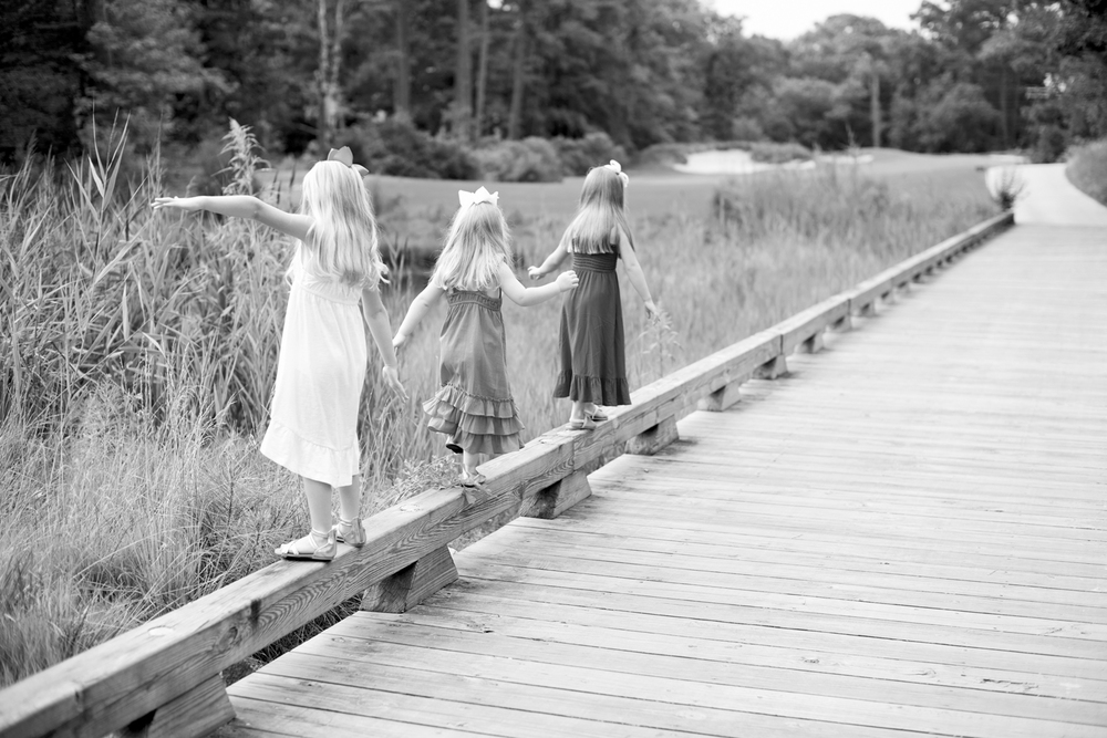 Little girls walking on a bridge in black and white