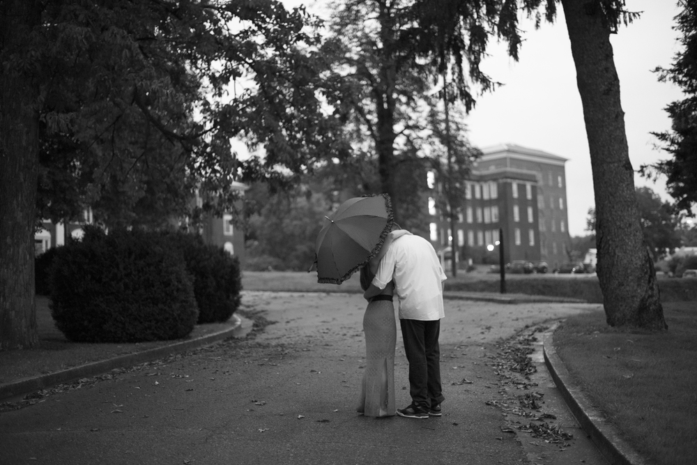 A polka dot umbrella hides a couple kissing during a beautiful engagement pictures in Downtown Staunton, Virginia (black and white)