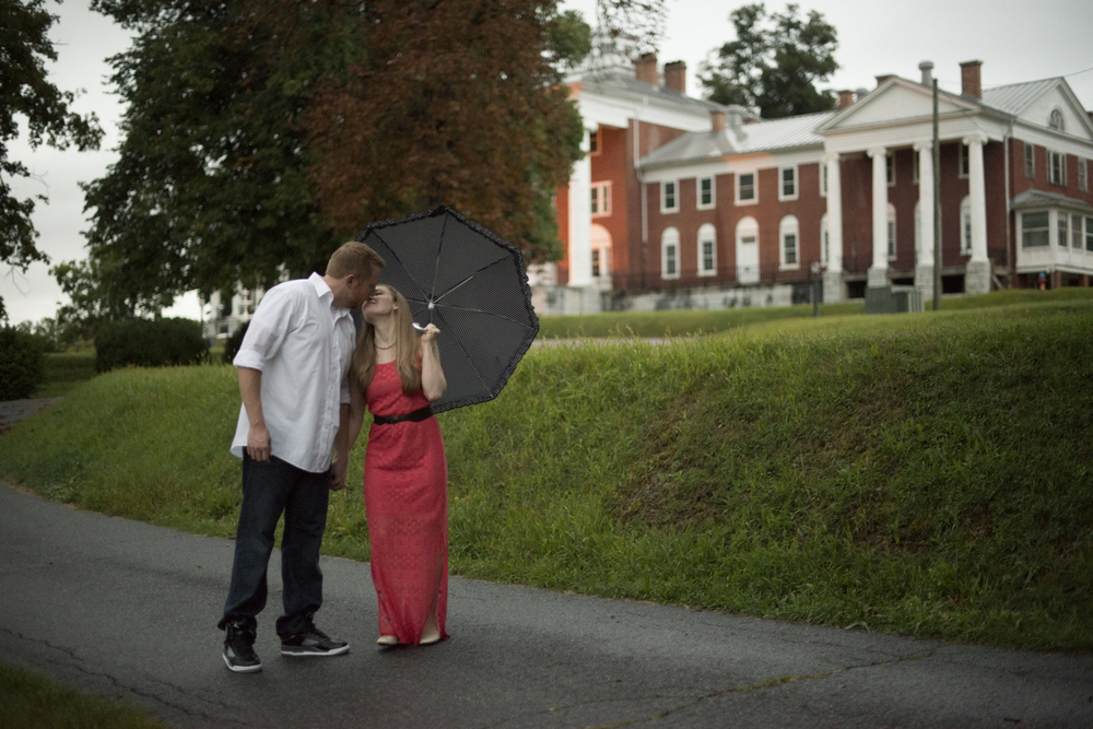 An engaged couple walks with a polka dot umbrella during a beautiful engagement pictures in Downtown Staunton, Virginia