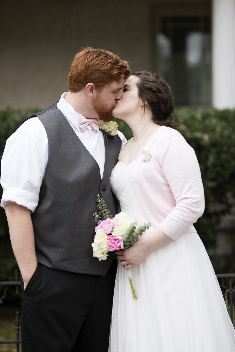 Bride, in her pink cardigan, and her groom kiss after their elopement