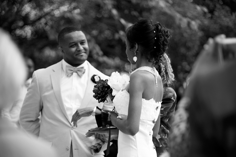 Bride meets her groom at the altar of their wedding ceremony (black and white)