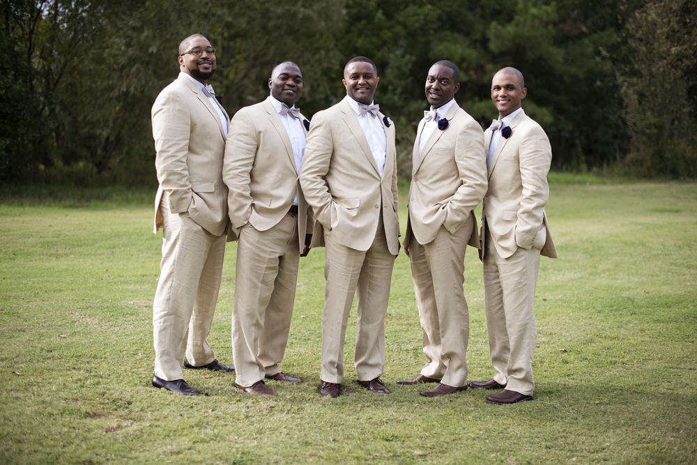 Groom with his groomsmen in light tan suits and purple bowties