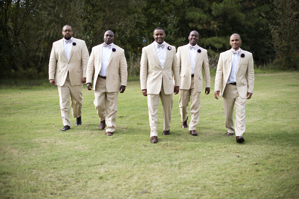 Groom walking with his groomsmen in light tan suits and purple bowties