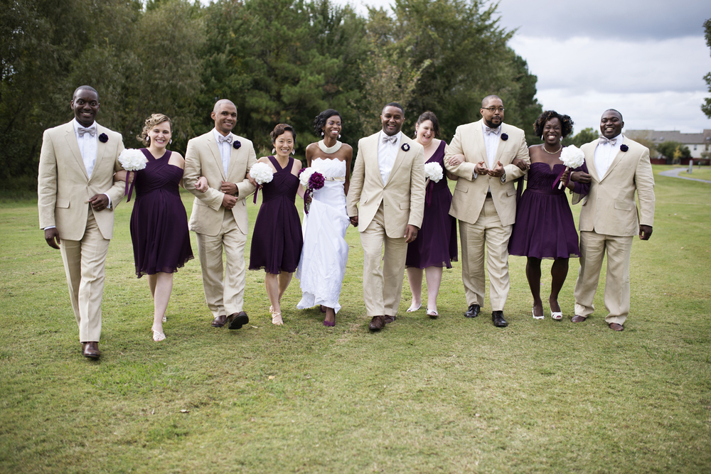 Bridal party in light tan suits and purple dresses after the wedding
