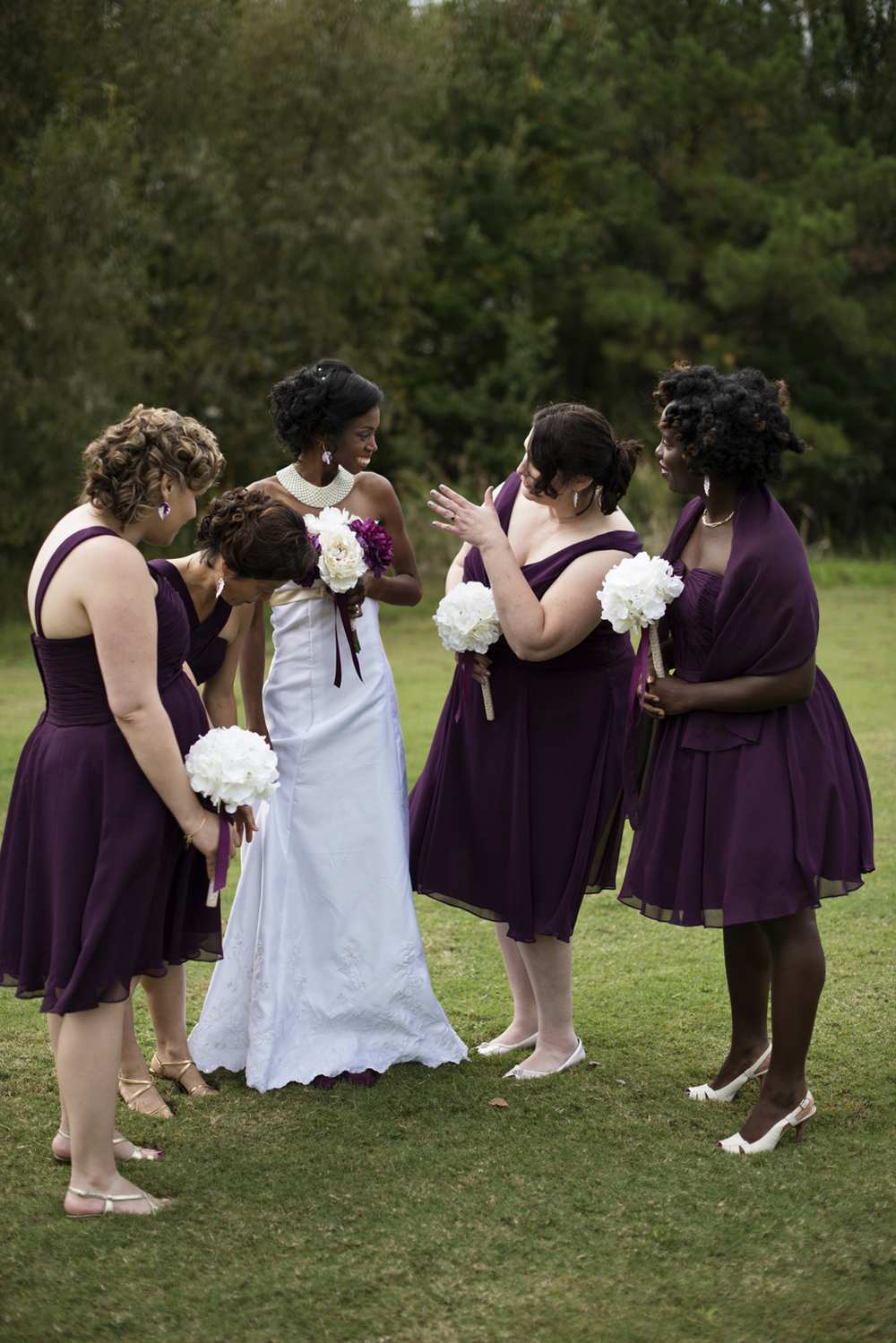 Bridesmaids gather around the bride in purple dresses and white flowers