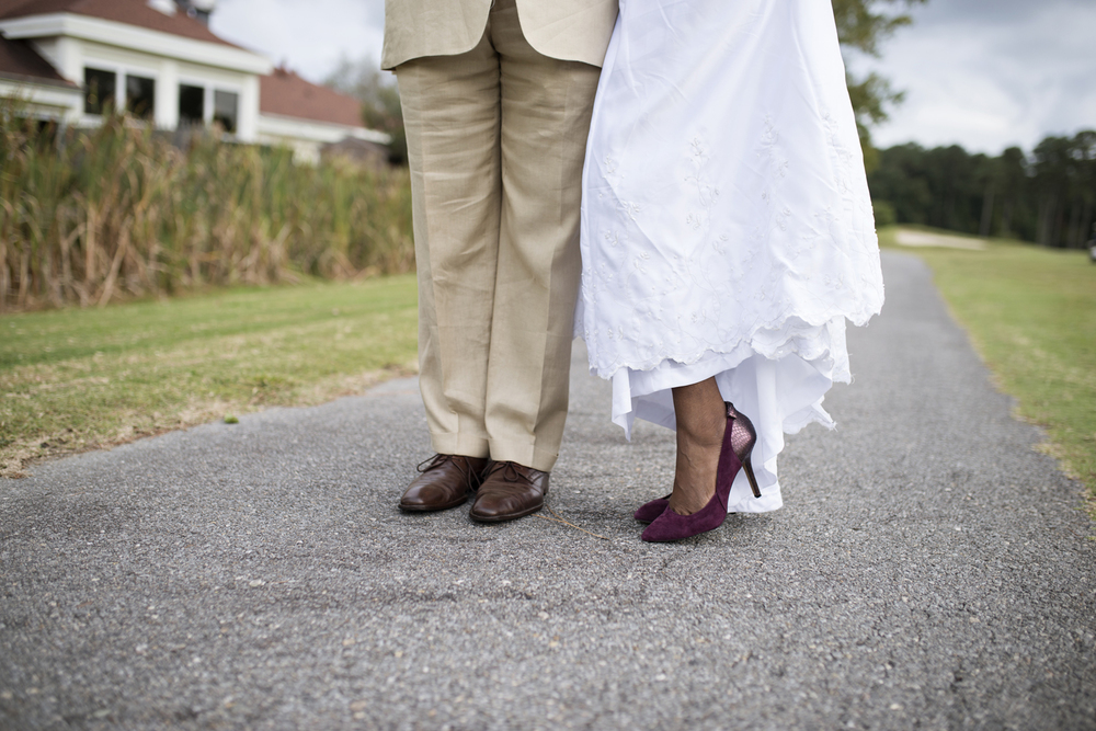 Dark brown shoes and purple heels at a wedding